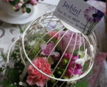 Cream bird cage filled with pink and purple flowers