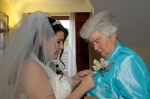 Bride pins corsage to the mother-of-the-bride's jacket