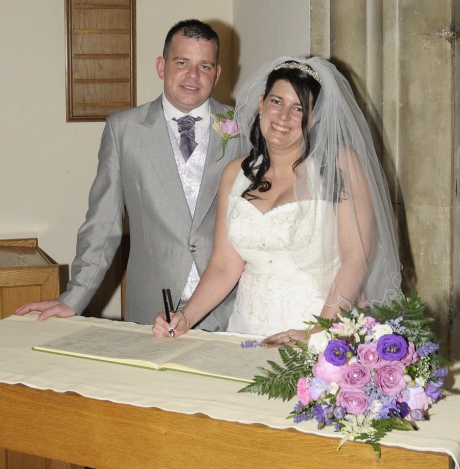 Bride and groom pose while signing the register
