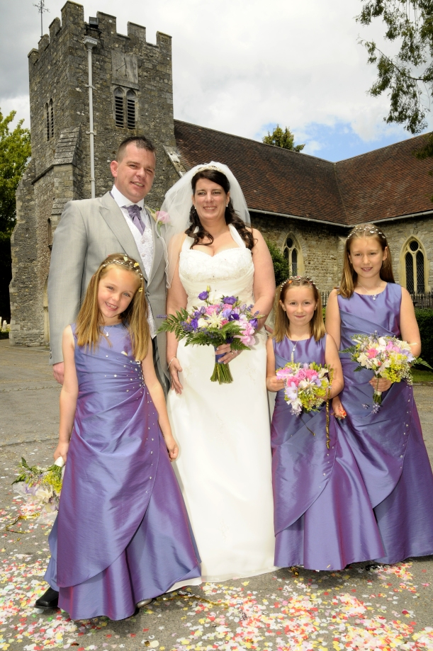 Bride, groom and bridesmaids pose outside church