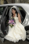 Bride in wedding dress steps out of car
