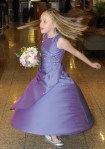 Young bridesmaid in purple dress dances holing posy