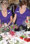 Two women prepare a flower display