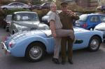 Two men in 1950s military uniform pose in front of a convertible sports car