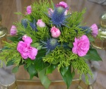 Flower arrangement with pink carnations and thistles